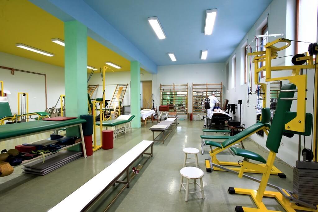 Palestra per la Fisioterapia Riabilitativa. Interno con panche, lettini, attrezzature, un medico, sullo sfondo, sta trattando un paziente