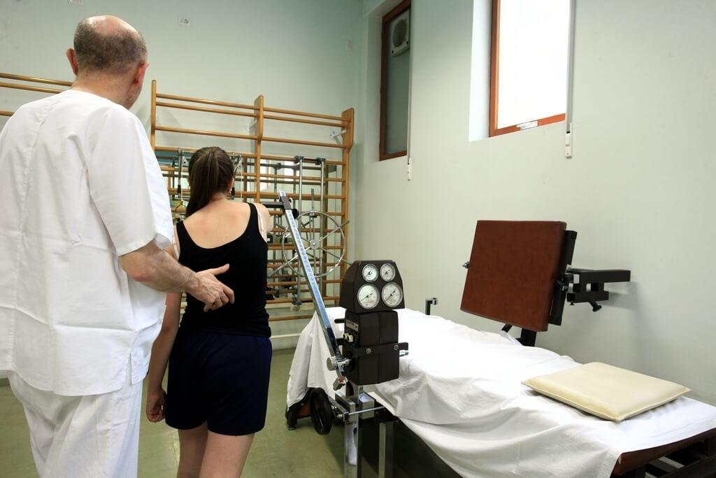 Un medico durante una seduta di riabilitazione motoria